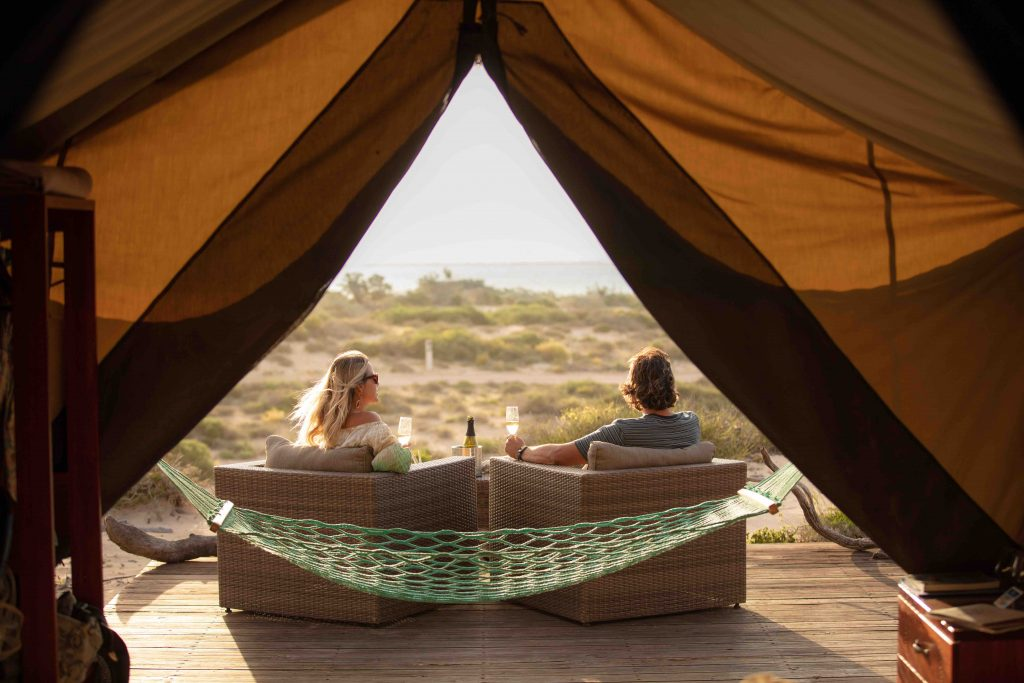 Sal Salis Camp View from inside tent out to beach-couple enjoying drink on deck